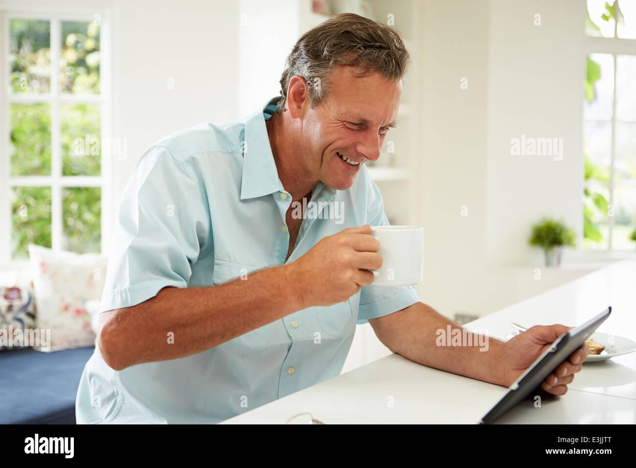 Applying Mann mit Digital-Tablette über Frühstück Stockbild