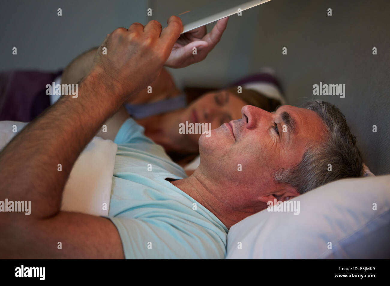 Applying paar im Bett mit Mann mit Tablet-PC Stockbild