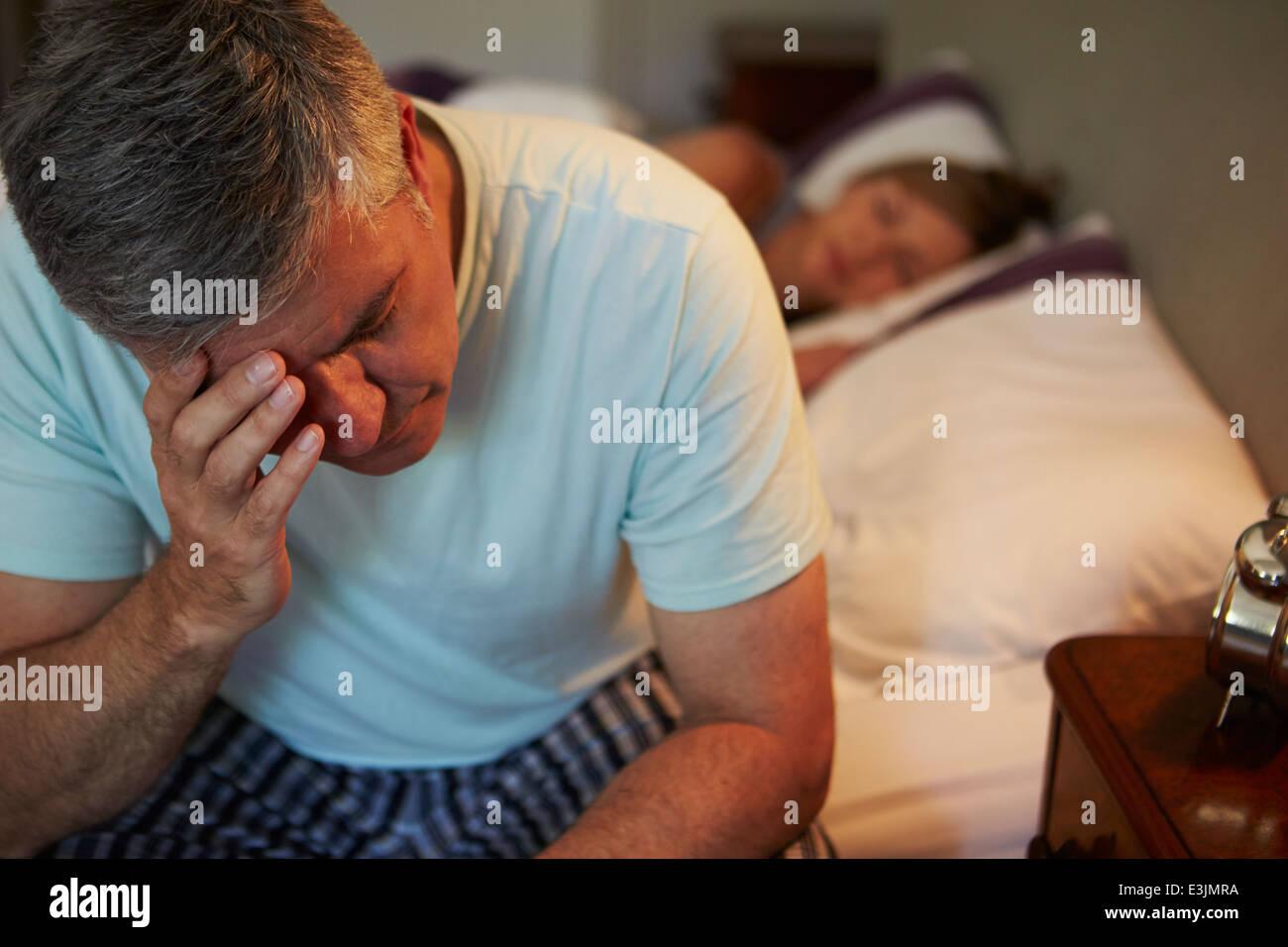 Mann wach im Bett leiden mit Schlaflosigkeit Stockbild