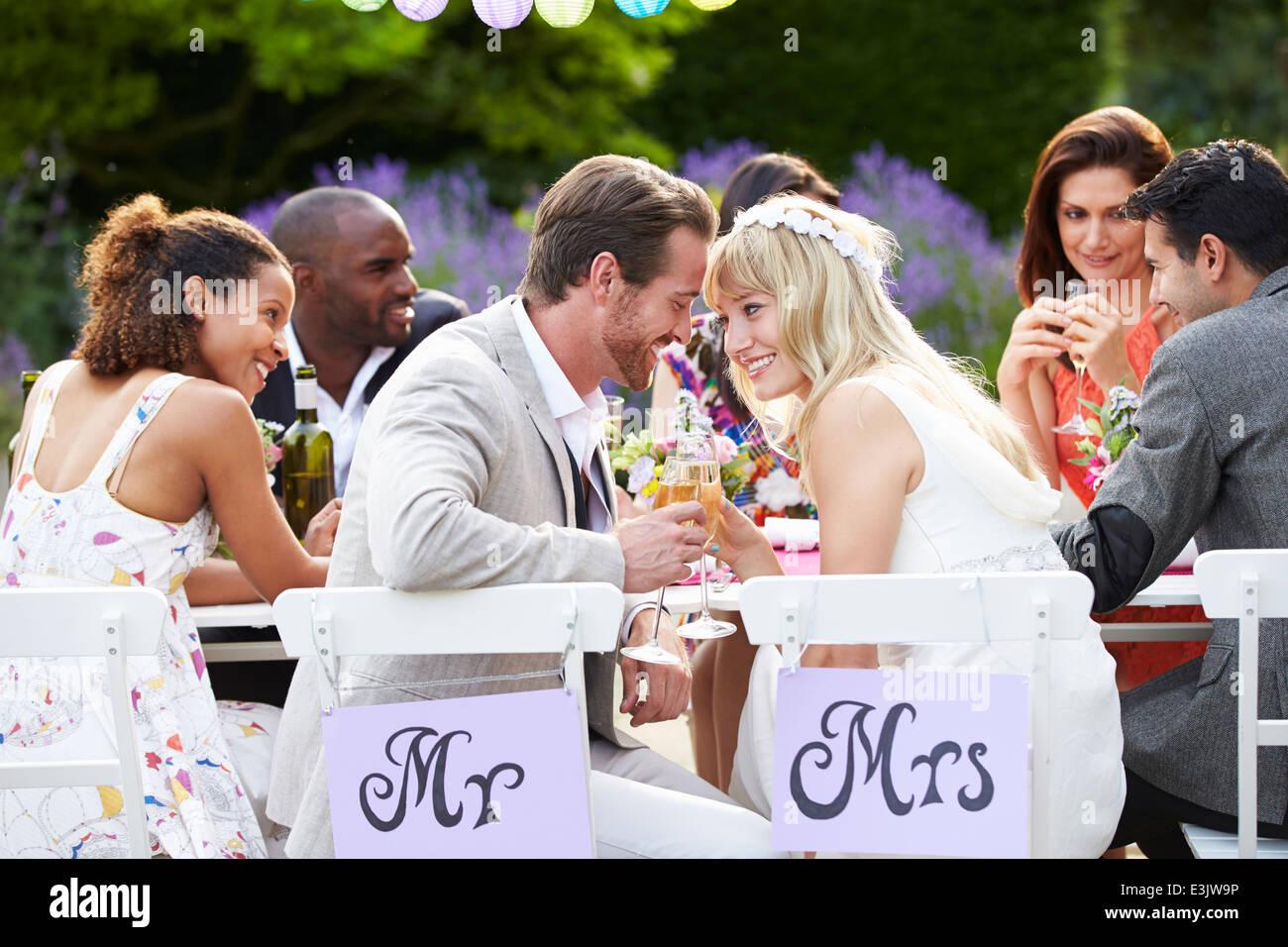 Braut und Bräutigam genießen Mahlzeit bei Hochzeitsfeier Stockbild