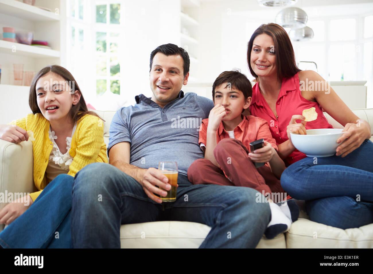 Hispanische Familie sitzt auf dem Sofa vor dem Fernseher zusammen Stockbild