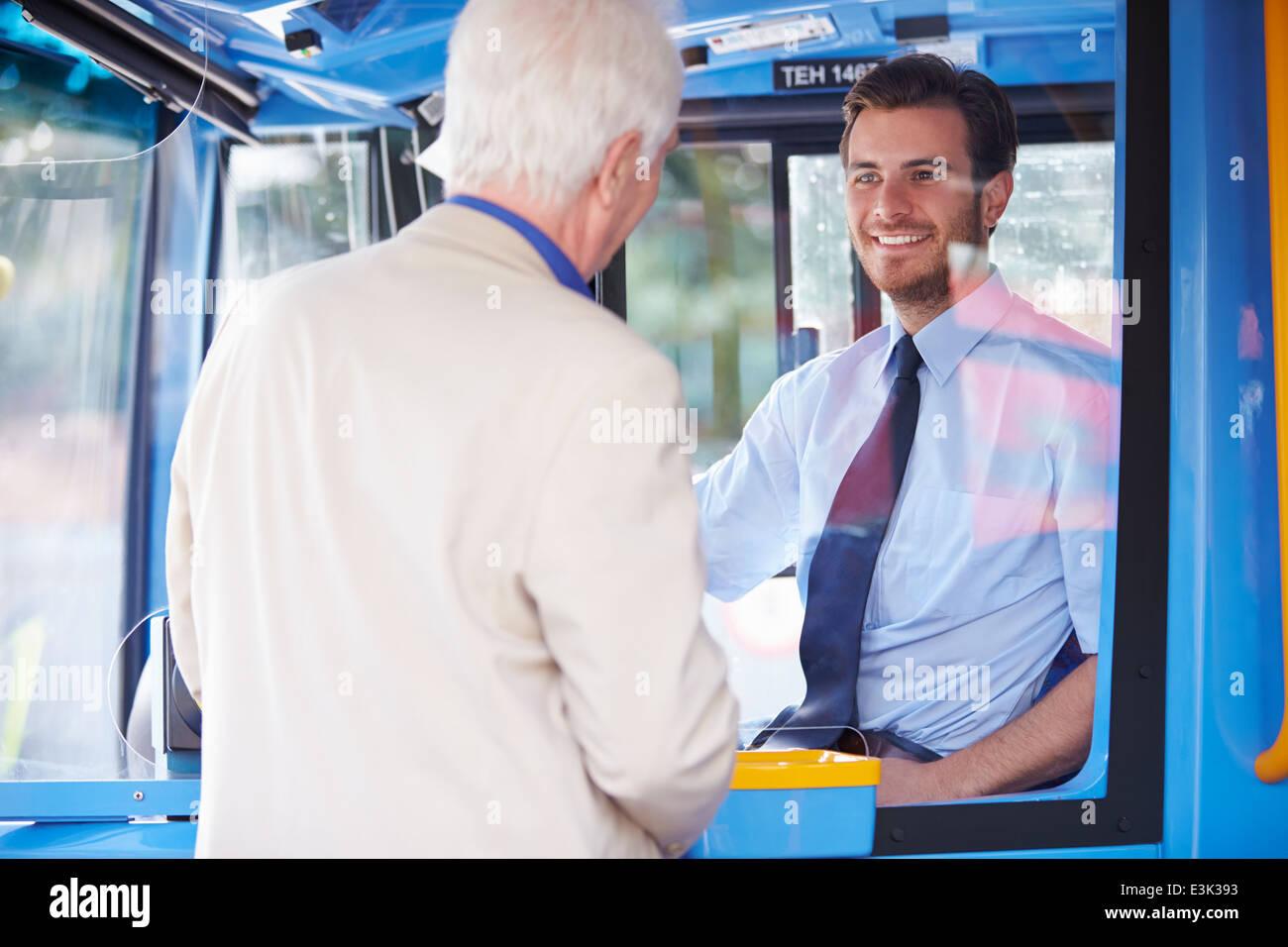 Senior woman einsteigen in Bus und Ticket kaufen Stockbild