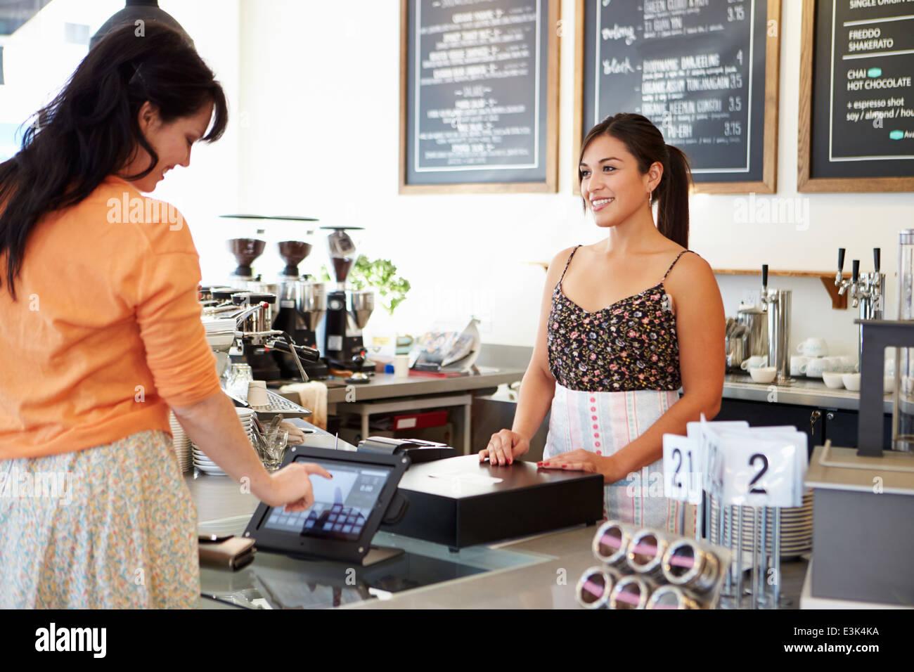 Kunden zahlen In Coffee-Shop mit Touchscreen Stockbild