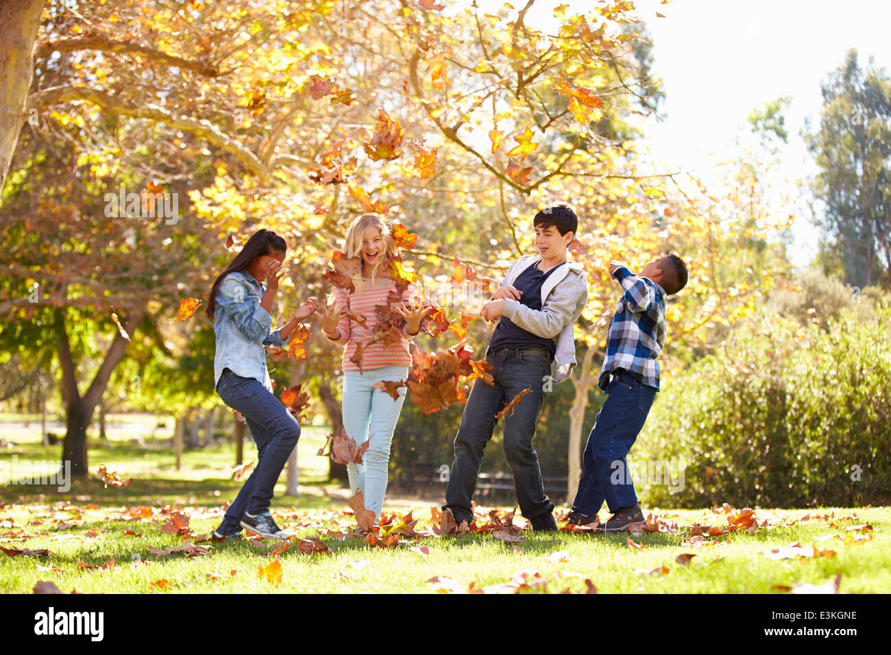 Vier Kinder, die Blätter im Herbst In die Luft werfen Stockbild