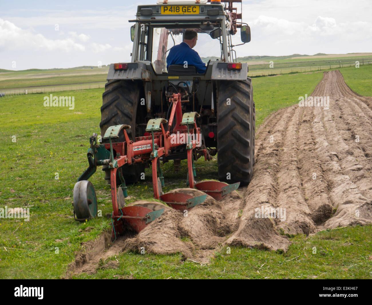 Traktorfahrer Pflügen auf North Uist Outer Hebrides Schottisches Hochland Stockfoto