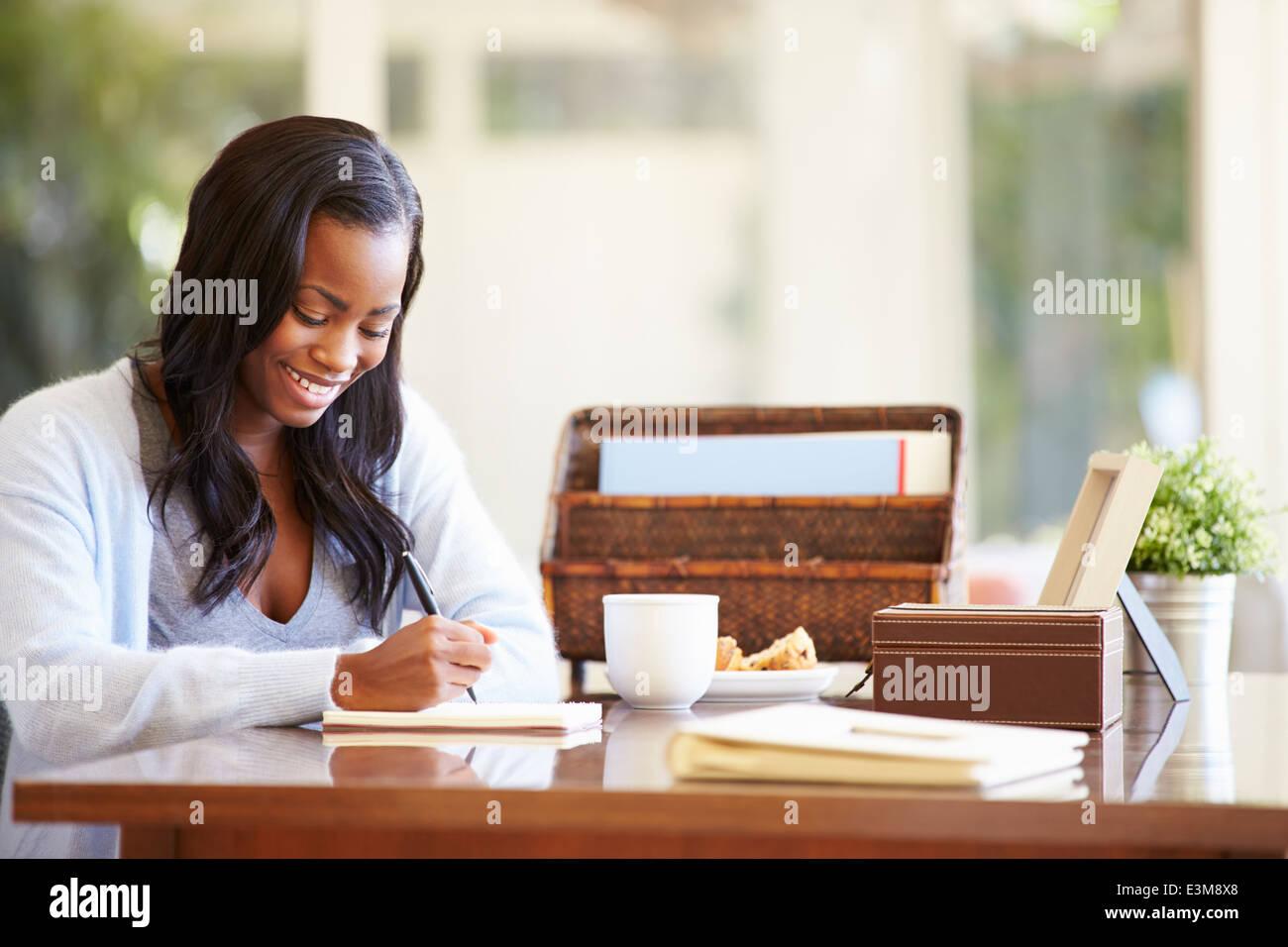 Frau schriftlich Notebook am Schreibtisch Stockbild