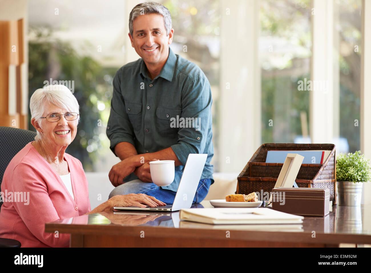 Erwachsenen Sohn helfende Mutter mit Laptop Stockbild