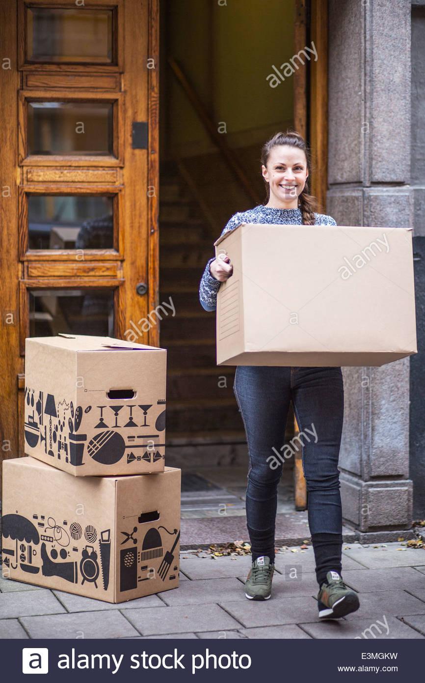 In voller Länge Portrait von junge Frau mit Karton zu Fuß auf dem Bürgersteig Stockbild
