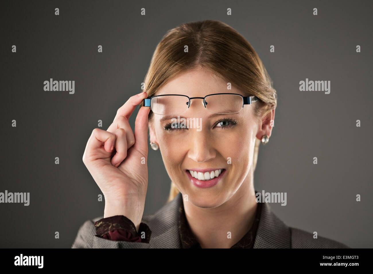 Porträt von zuversichtlich Geschäftsfrau, die Erhöhung der Brillen Stockbild
