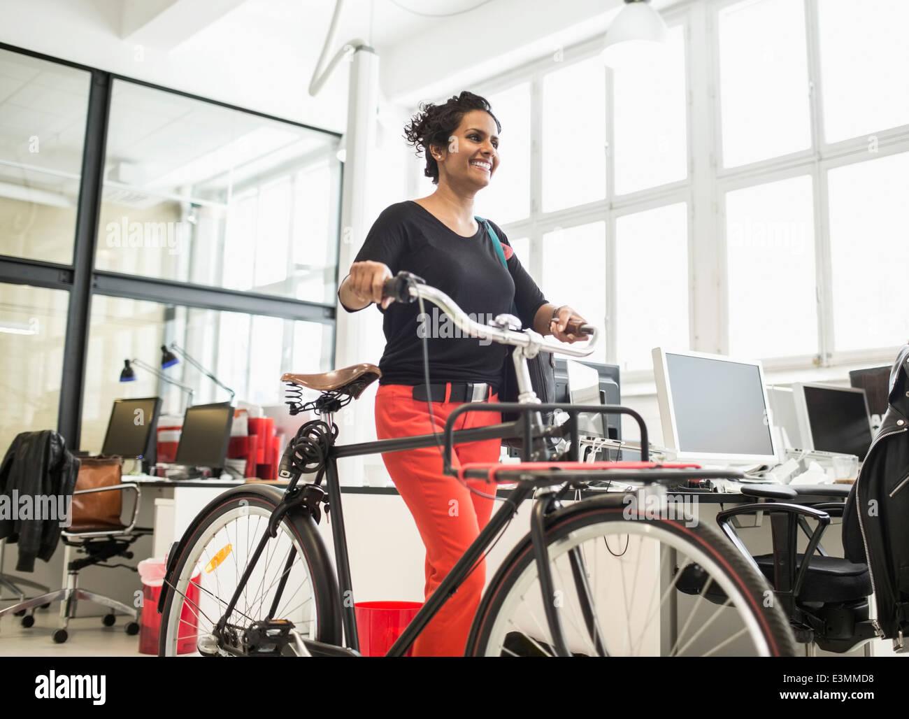 Lächelnd Geschäftsfrau mit dem Fahrrad, zu Fuß in Kreativbüro Stockbild