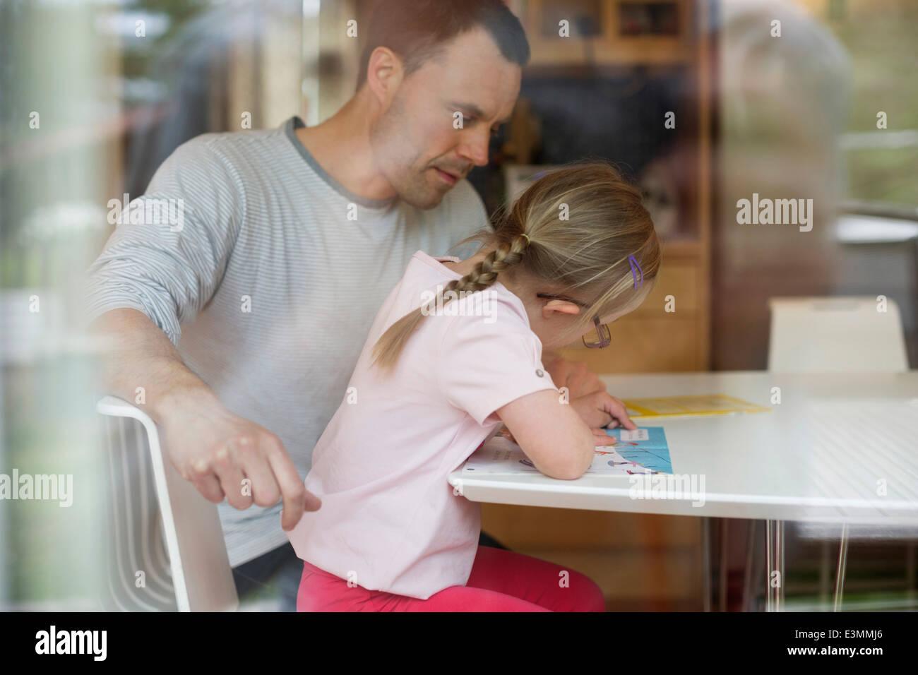 Vater unterstützen behinderte Mädchen in Studien am Tisch Stockbild