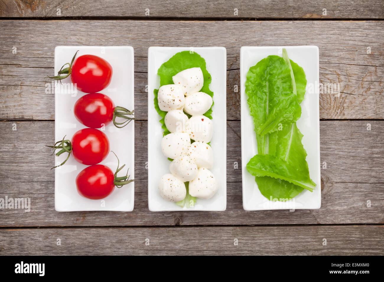 Tomaten, Mozzarella und grünem Salat Blätter auf Holztisch Hintergrund Stockbild