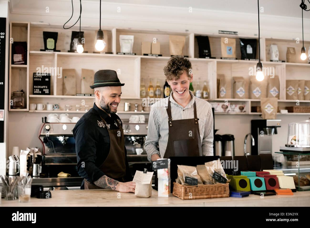 Glückliche Arbeiter arbeiten am Café-Schalter Stockbild