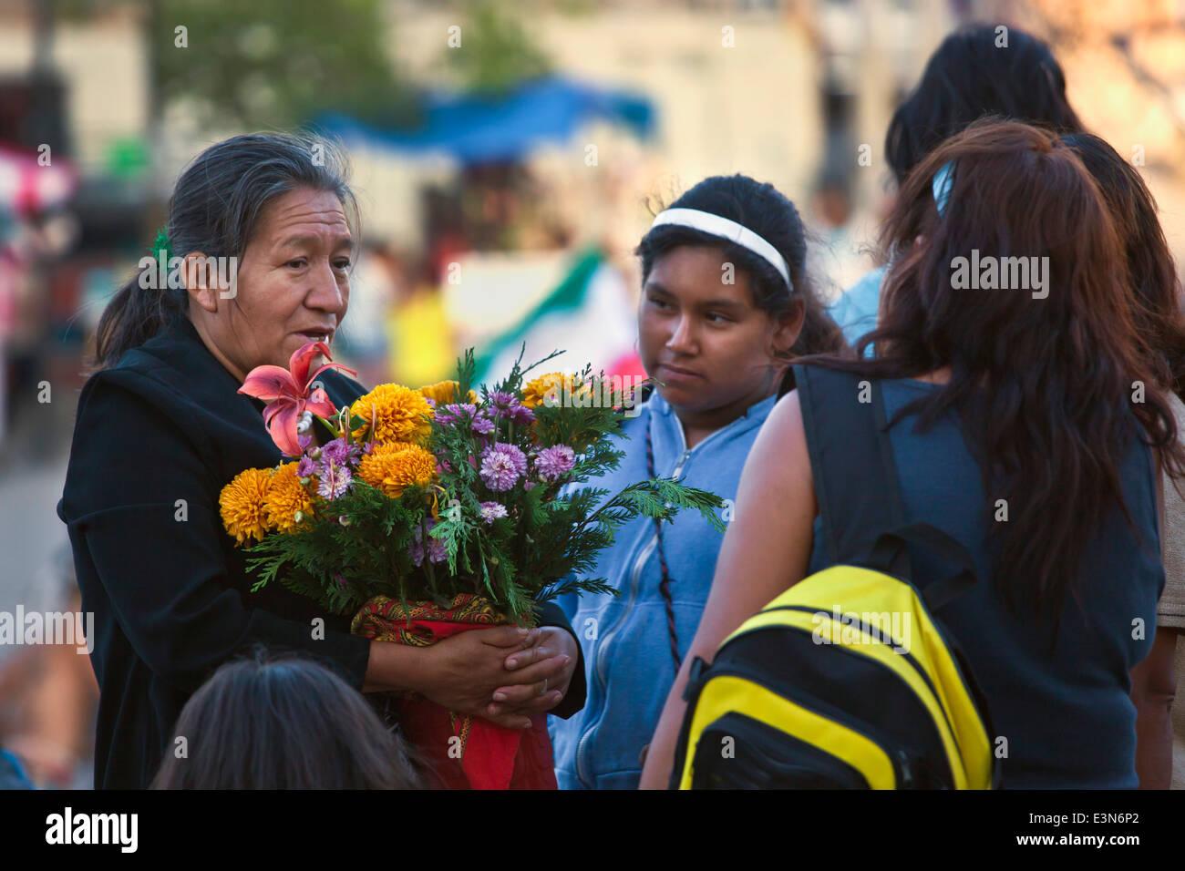 Eine Frau, die Blumen während der DIA DE LOS LOCOS Feier - SAN MIGUEL DE ALLENDE, GUANAJUATO, Mexiko Stockbild