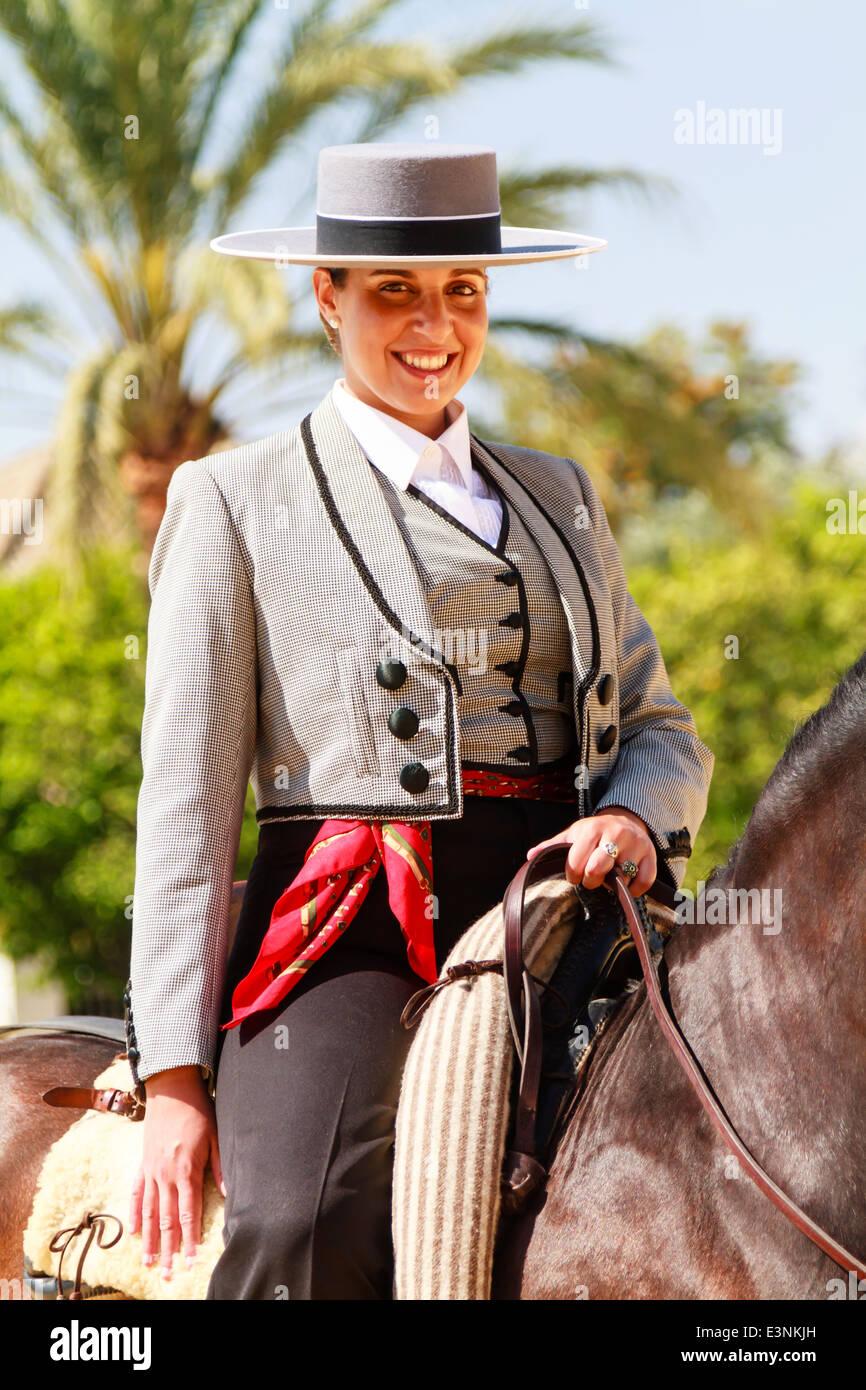 Reiterin in traditionellen abgeflachter Hut sitzt auf ihrem Pferd Lächeln während der Feria del Caballon geschmückt. Stockfoto