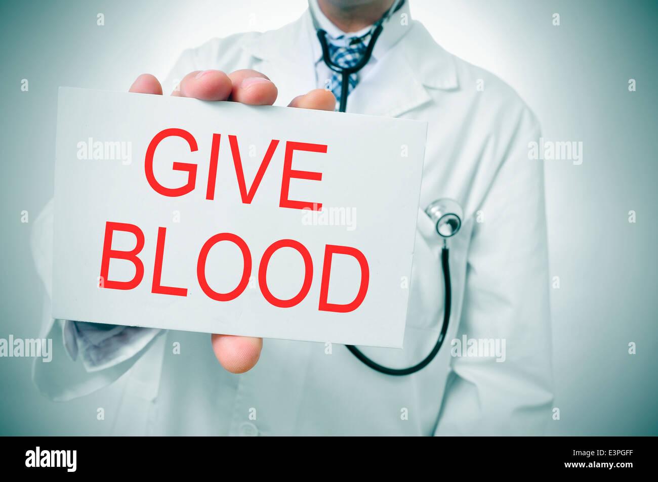 ein Arzt zeigt ein Schild mit dem Satz geben Blut geschrieben Stockbild
