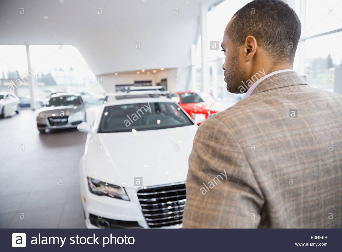 Man betrachtet man Autos im Autohaus Autohaus Stockbild