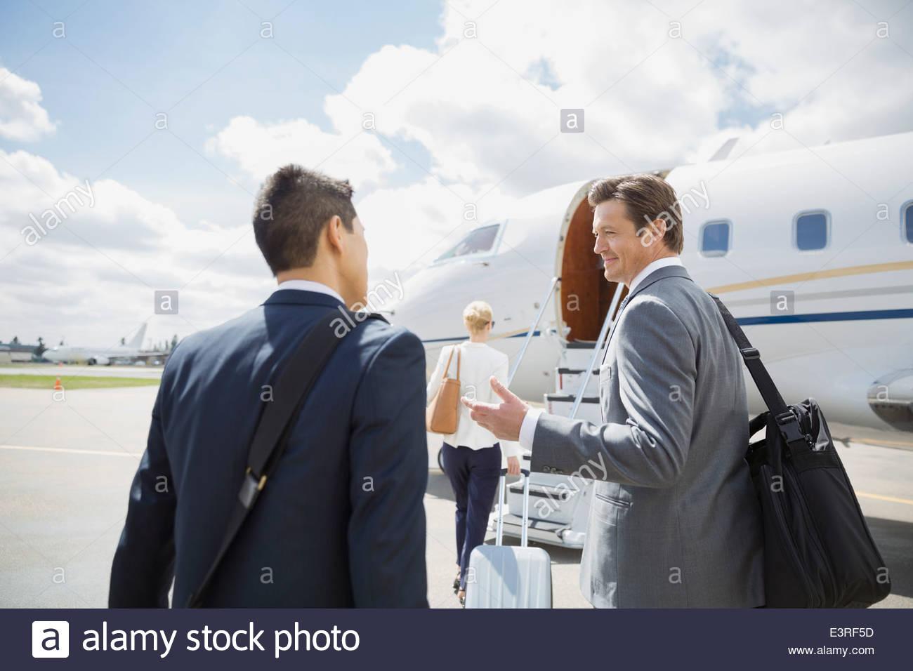 Geschäftsleute sprechen auf Asphalt mit corporate Jets Stockbild