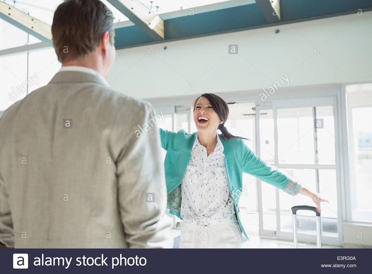 Begeisterte Frau Gruß Mann in Flughafen Stockbild
