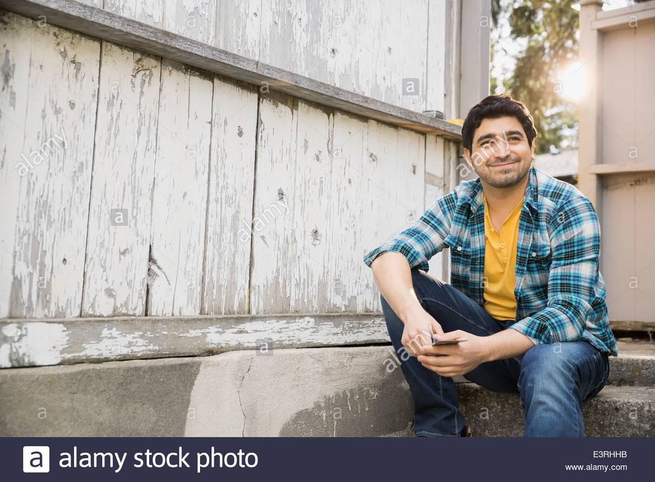 Lächelnder Mann sitzen durch Zaun mit abgeplatzte Farbe Stockbild