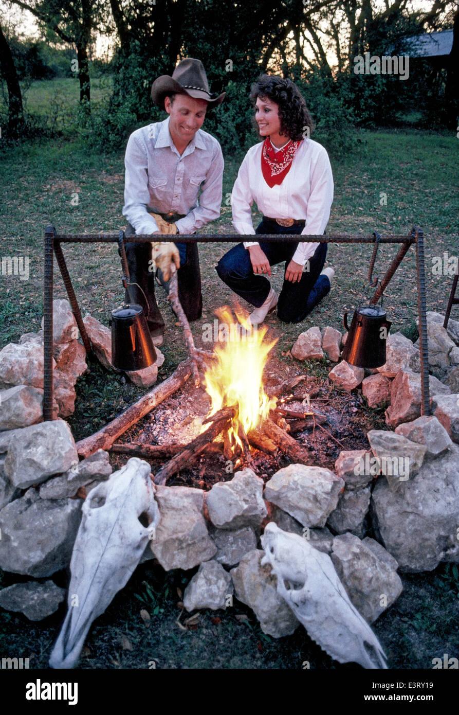 Eine amerikanische Cowboy und seine Freundin starten ein Abend am Lagerfeuer auf seinem Viehranch in der Nähe von Stockfoto