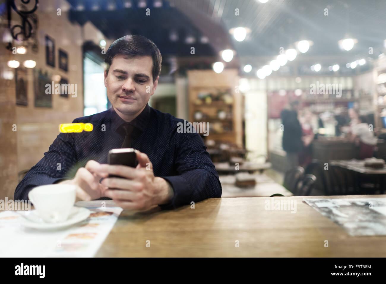 Mann am Tisch mit Telefon Stockbild