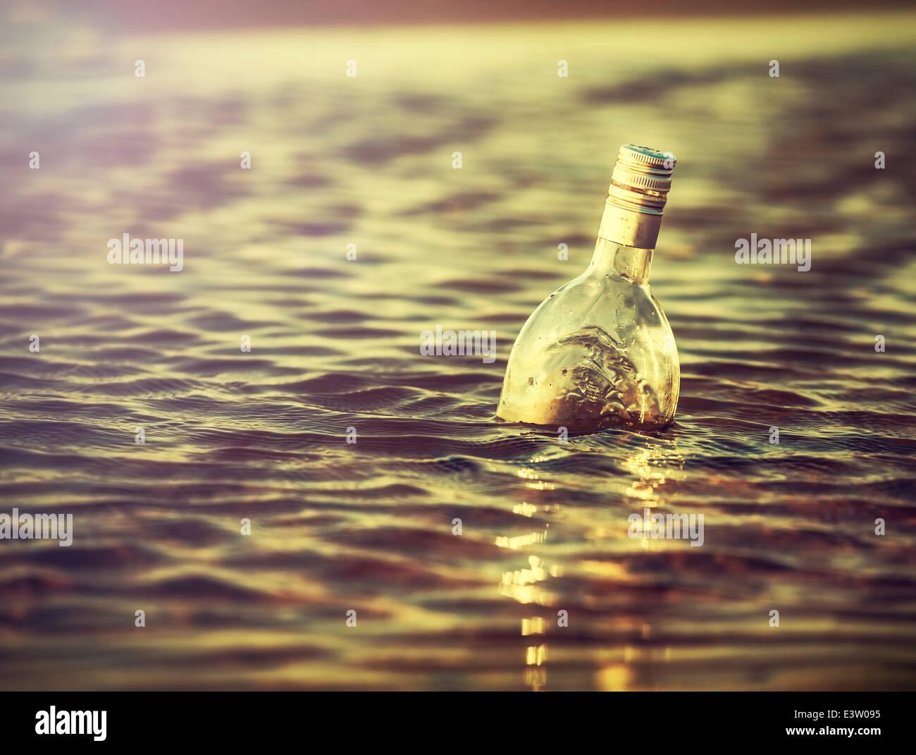 Flasche im Wasser bei Sonnenuntergang, Retro-Instagram-Vintage-Effekt. Stockbild