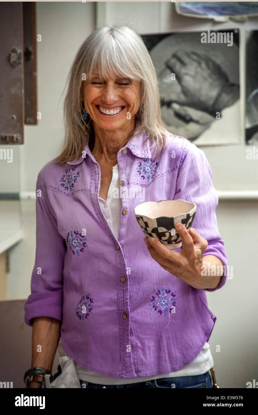 Ein Keramik-Gymnasiallehrer in San Clemente, Kalifornien, lacht, als sie ihre Schüler ein Beispiel für Stockbild
