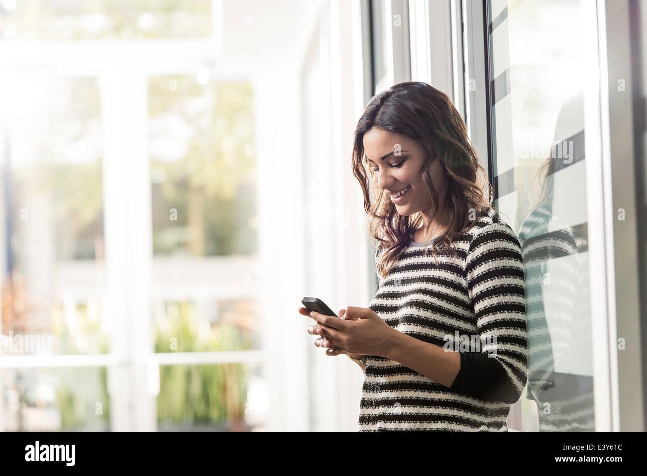 Junge Geschäftsfrau SMS auf Smartphone im Büro Stockbild