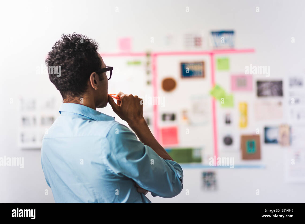 Junger Mann studieren Wand der Notizen im Büro Stockbild