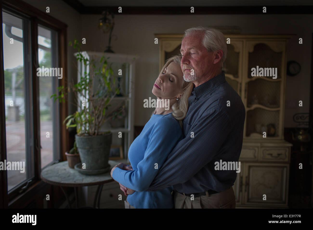 Romantische älteres paar umarmt mit Augen geschlossen im Speisesaal Stockbild
