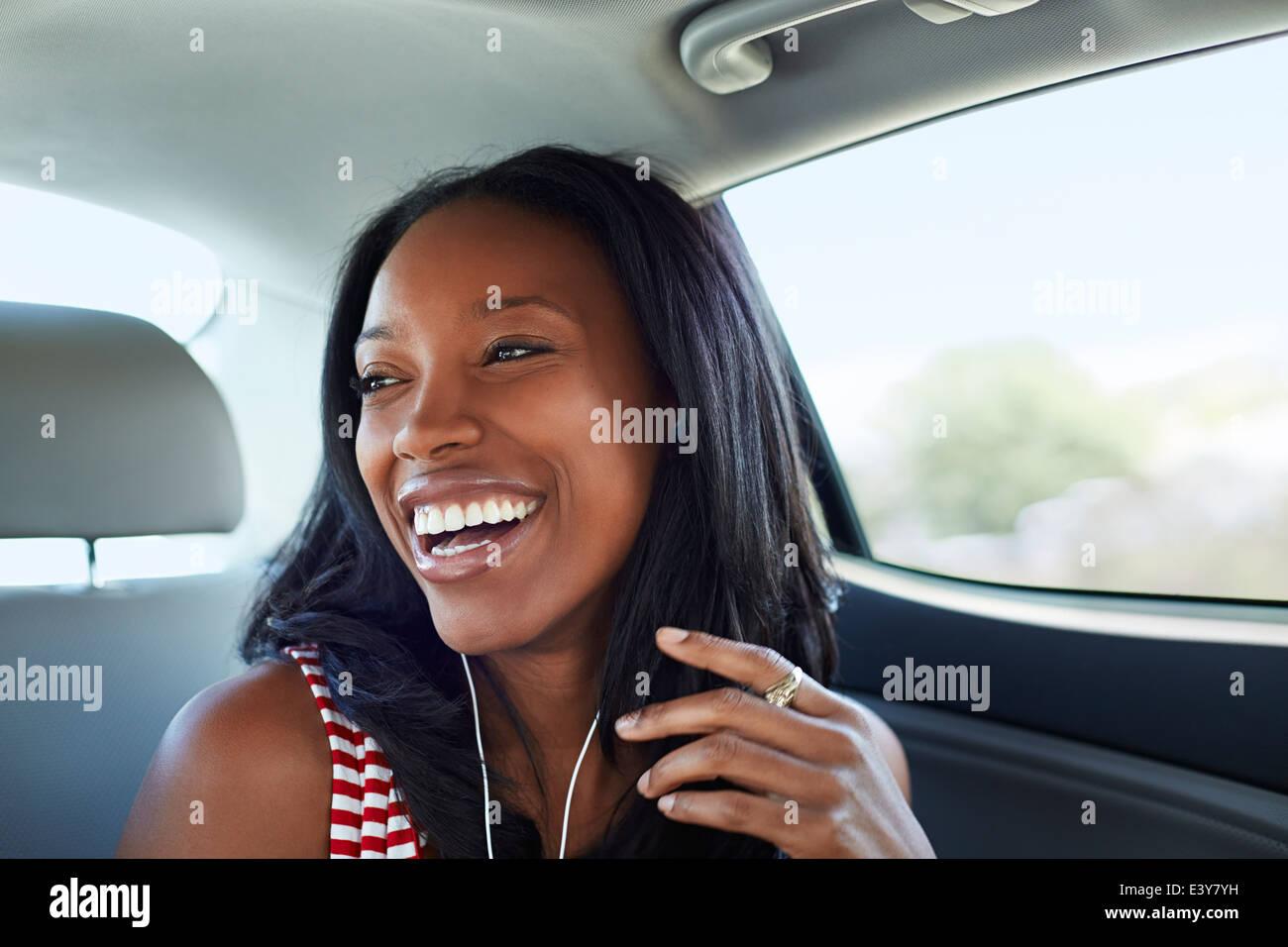 Junge Frau lachend Auto Rücksitz Stockbild