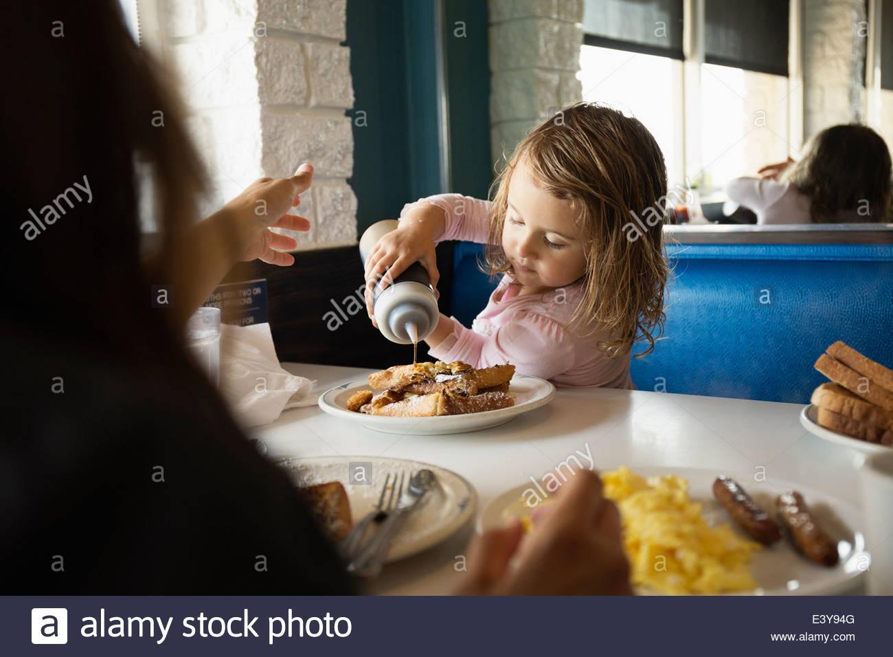 Mutter mit Kleinkind Tochter strömenden Ketchup im diner Stockbild