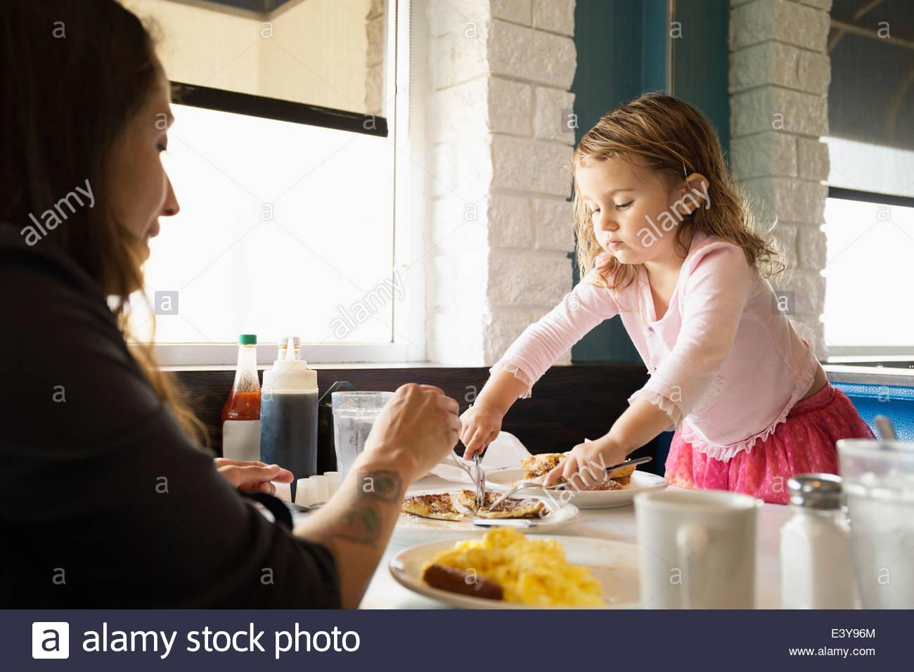 Mutter und Kleinkind Tochter Essen im diner Stockfoto