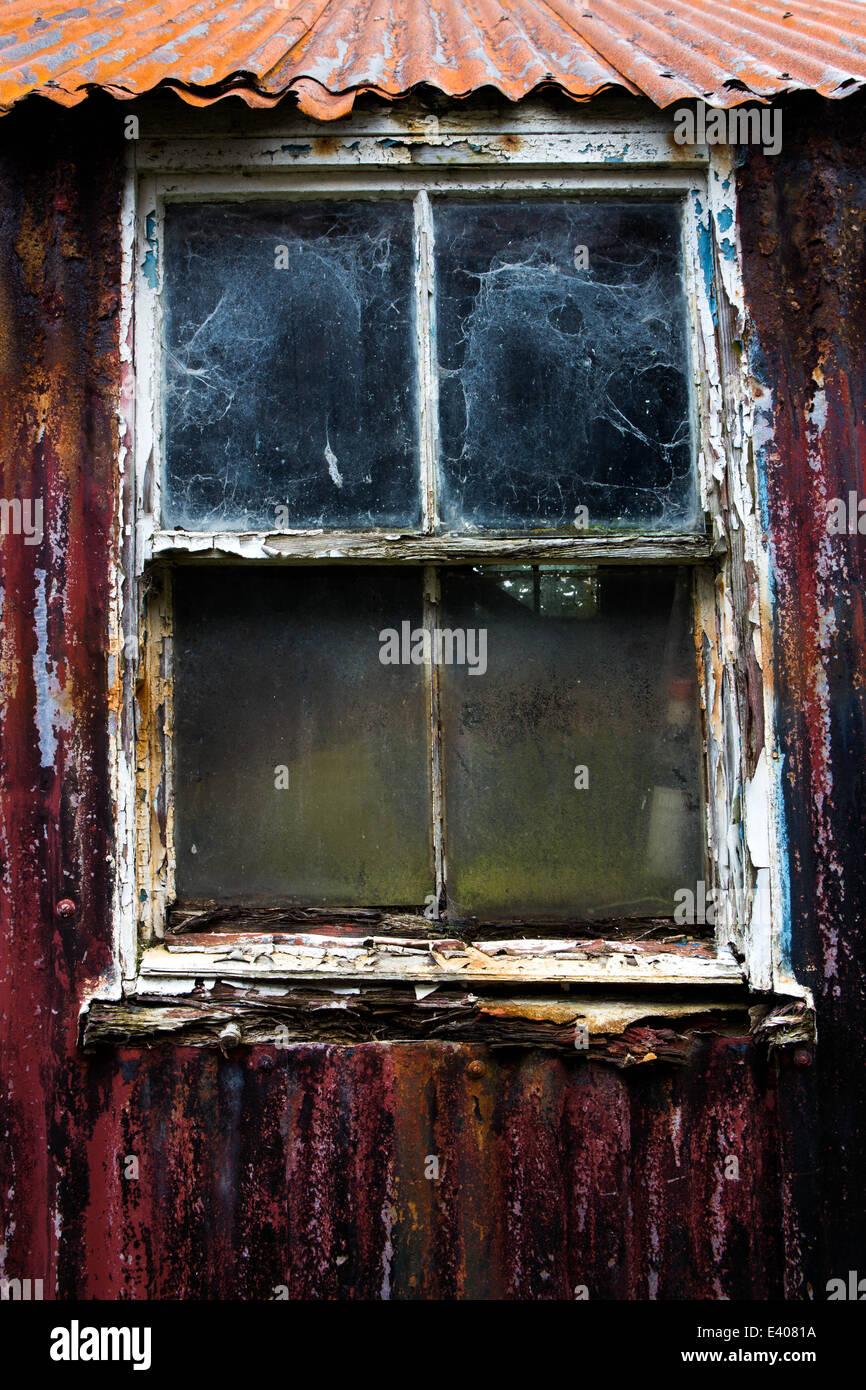Alte Fensterrahmen in einem gewellten Zinn Gebäude verrotten ...