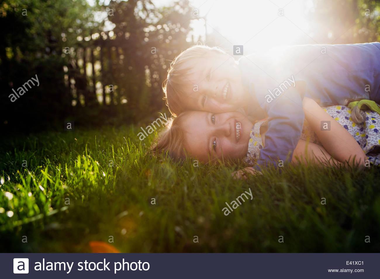 Bruder und Schwester liegen auf dem Rasen, umarmen Stockfoto