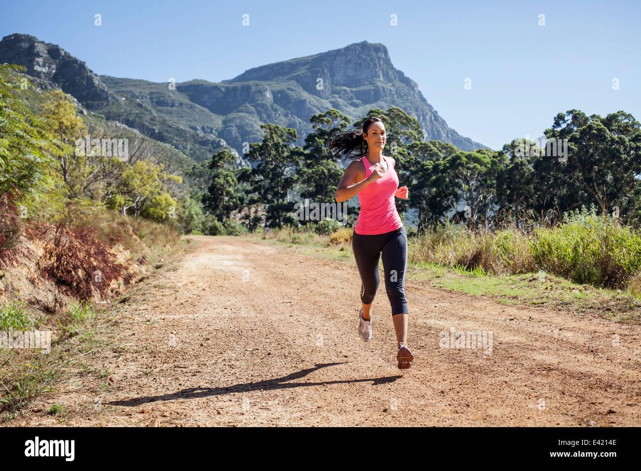 Junge Frau im Wald joggen Stockbild