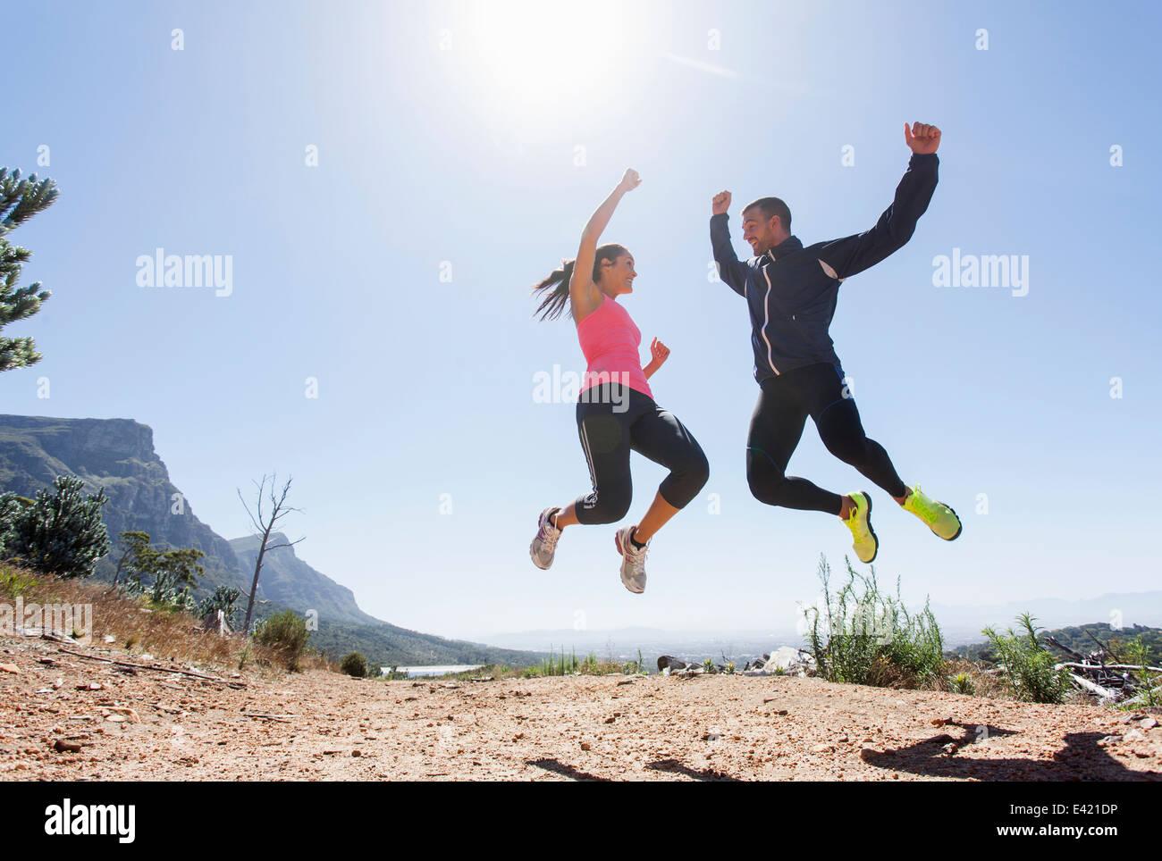 Junge Jogger springen in der Luft Stockbild