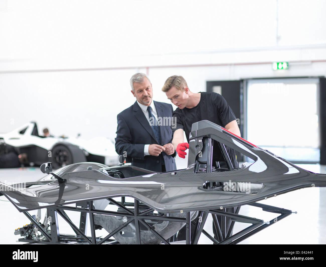 Manager und Ingenieur Inspektion Kohlefaser-Karosserie von Supersportwagen im Sportwagen-Fabrik Stockbild