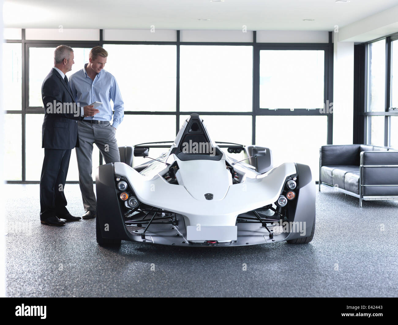 Vertriebsmitarbeiter mit Kunden Supersportwagen im Show-room Stockbild