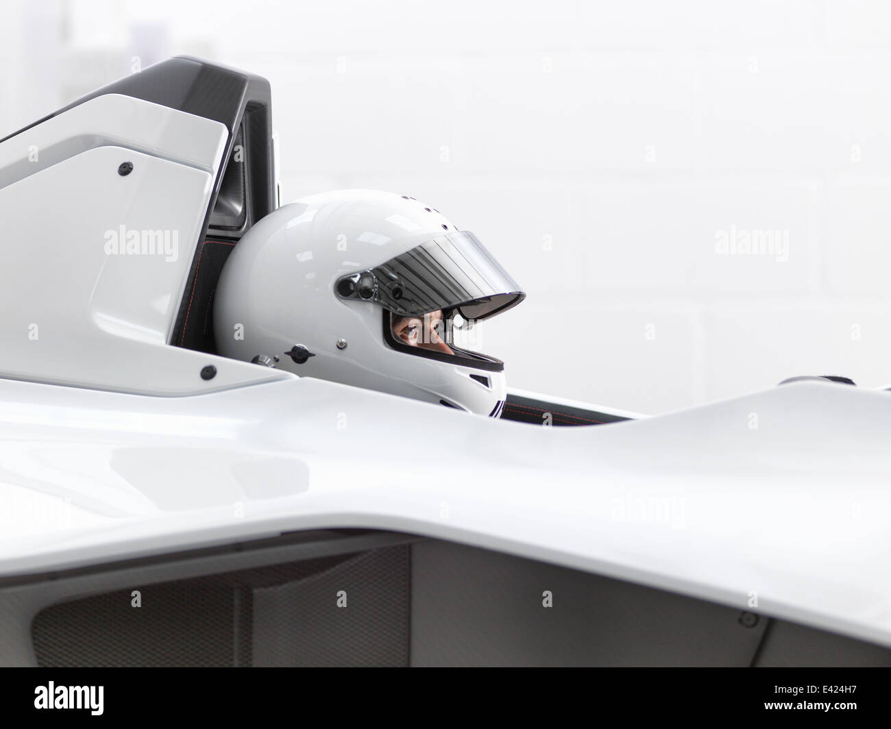 Testfahrer im Helm in Supersportwagen Stockbild