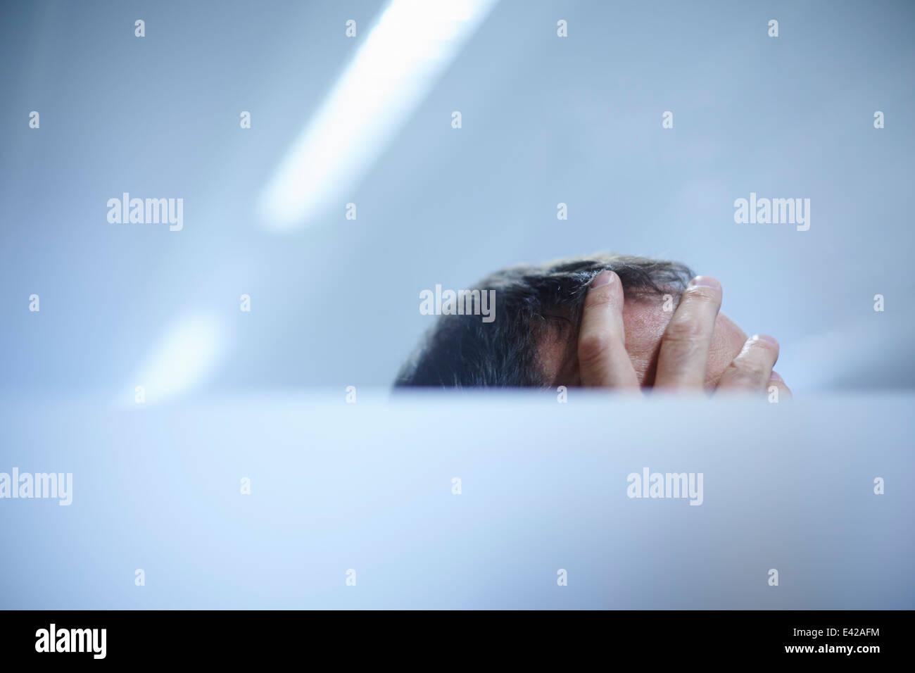 Hand auf der Stirn des Mannes Stockbild
