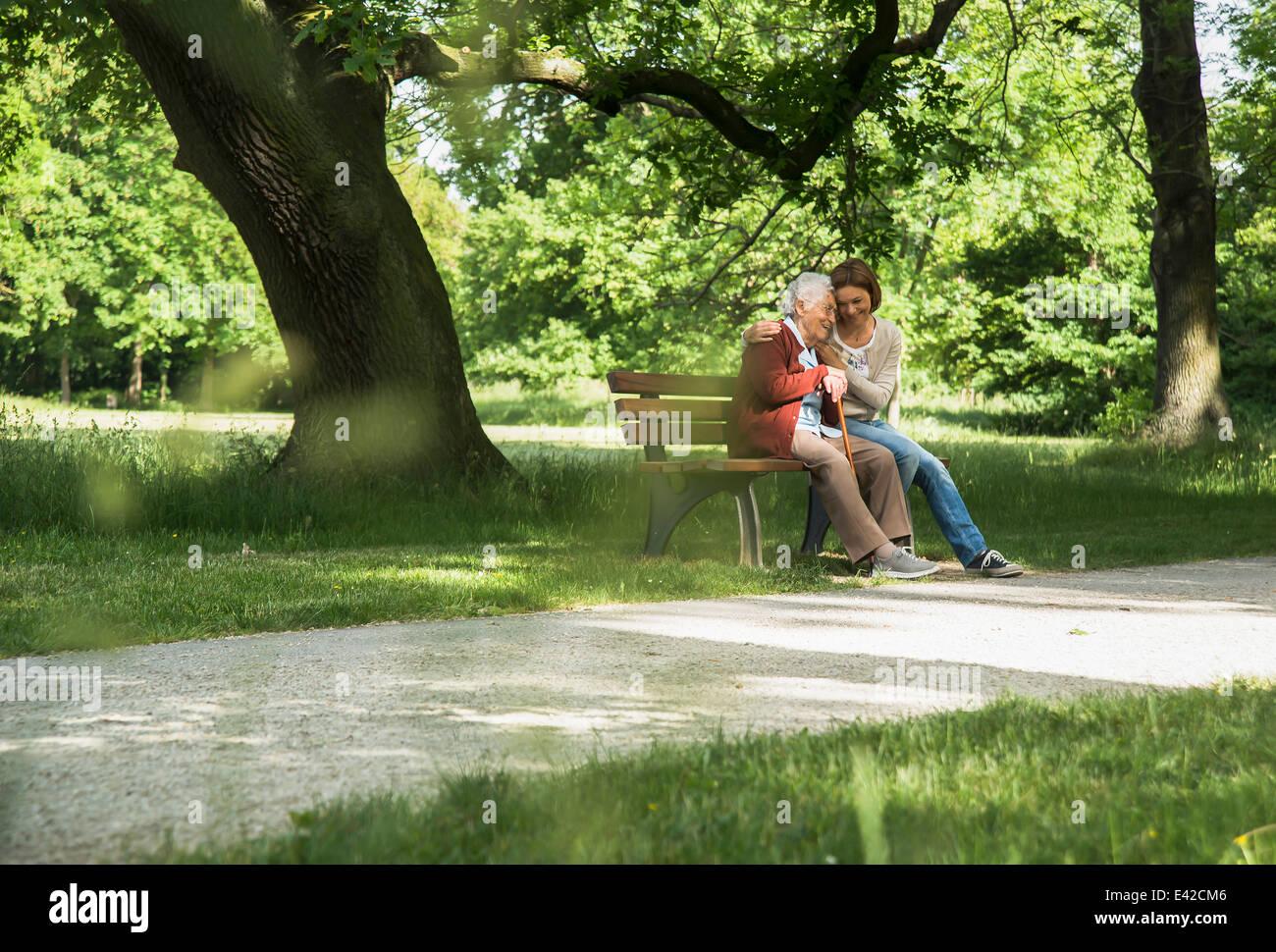 Ältere Frau sitzen auf der Parkbank mit Enkelin Stockbild