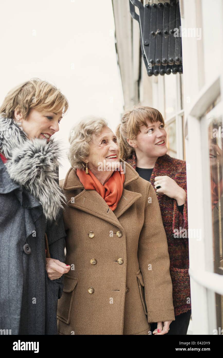 Ältere Frau mit Tochter und Enkelin, suchen Sie im Fenster Stockbild
