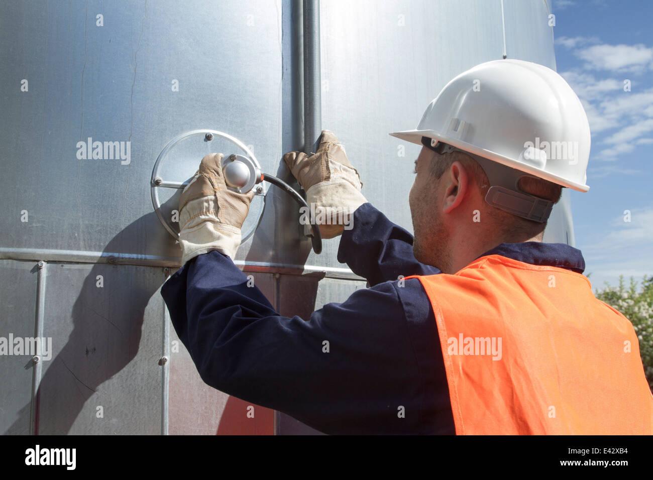 Rückansicht des Technikers Überwachung Rohre außerhalb Kraftwerk Stockbild