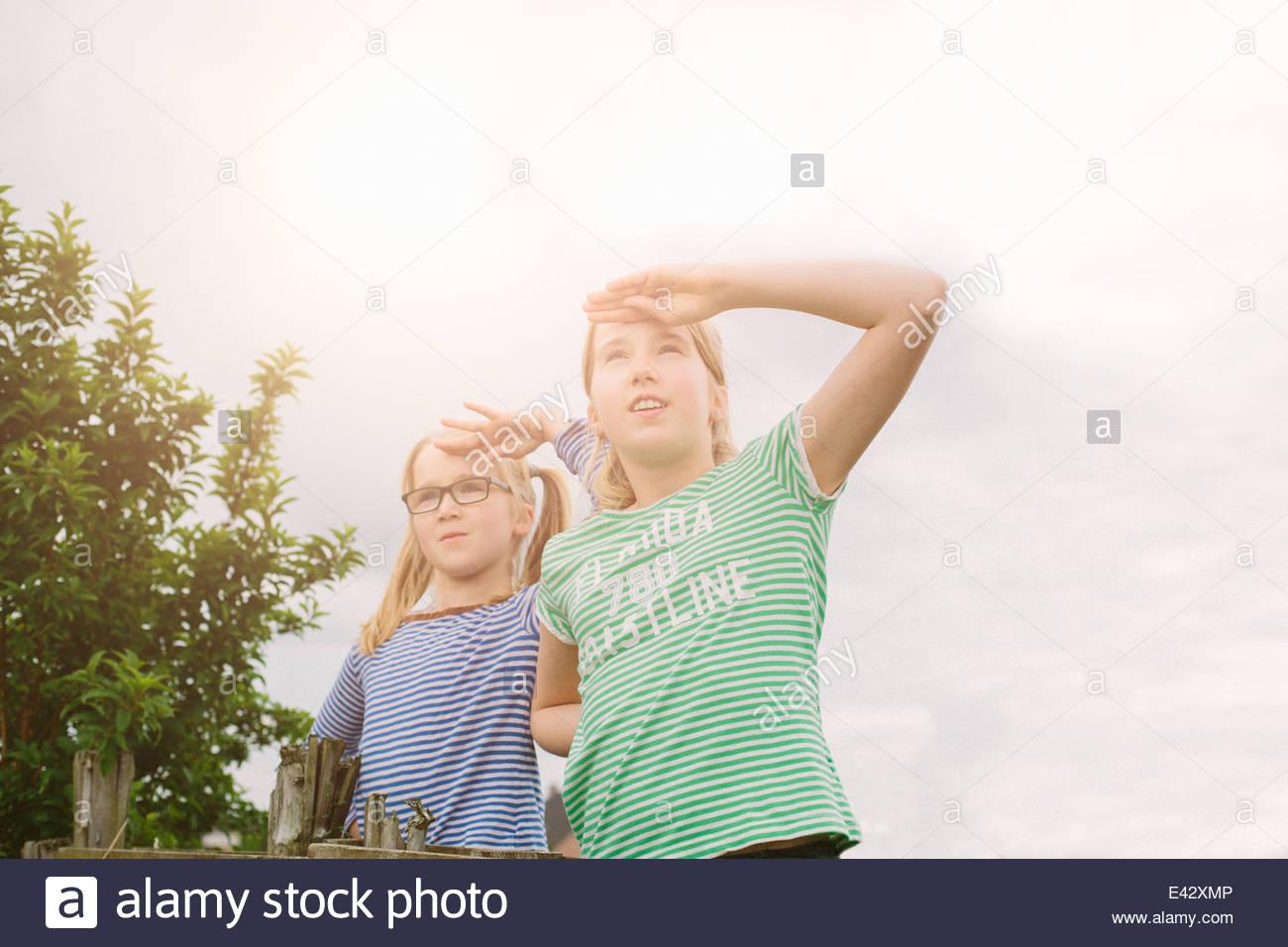 Porträt von neun Jahre altes Mädchen und Schwester Abschirmung Augen im Feld Stockbild