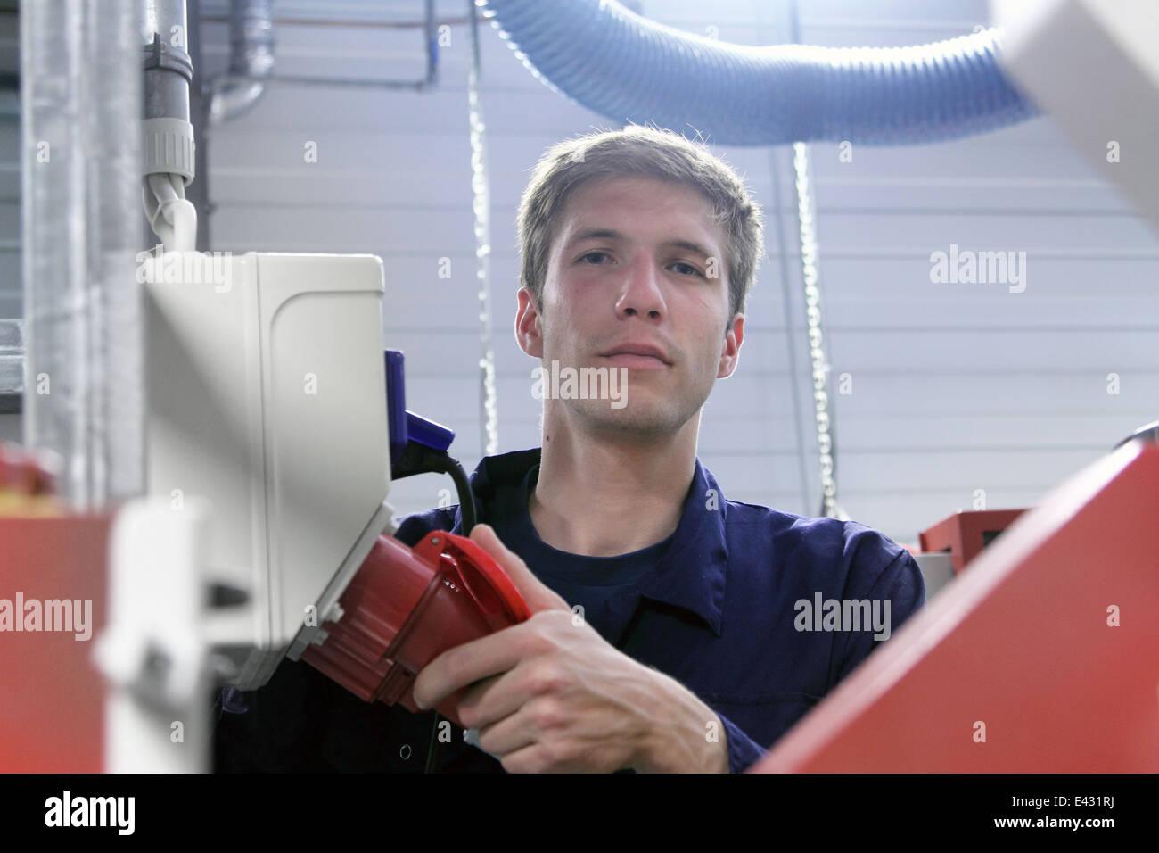 Porträt von männlichen Elektriker und Stromversorgungskabel in Fabrik Stockbild