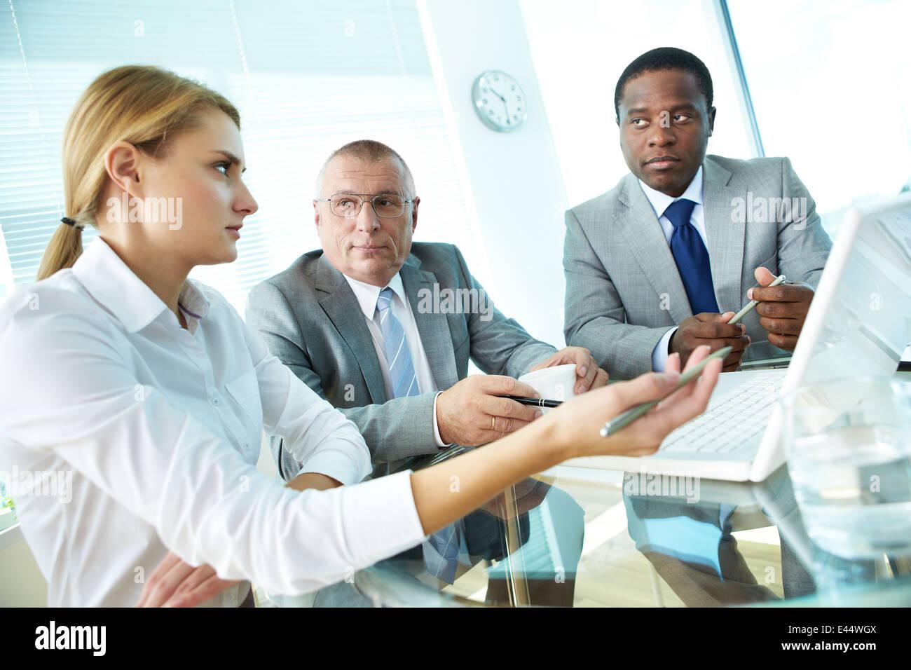 Porträt von hübschen Sekretärin zeigt auf Laptop-Bildschirm etwas zu ihrem Chef und Kollegen zu erklären Stockfoto