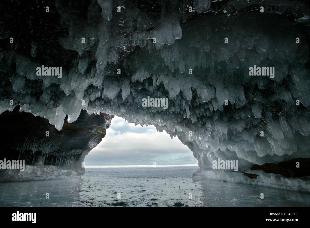 Eis hängen von Bogen in Meereshöhle geschnitzt in weichem Sandstein-Klippen, zugefrorenen See, Squaw Bay, Lake Superior, Stockfoto