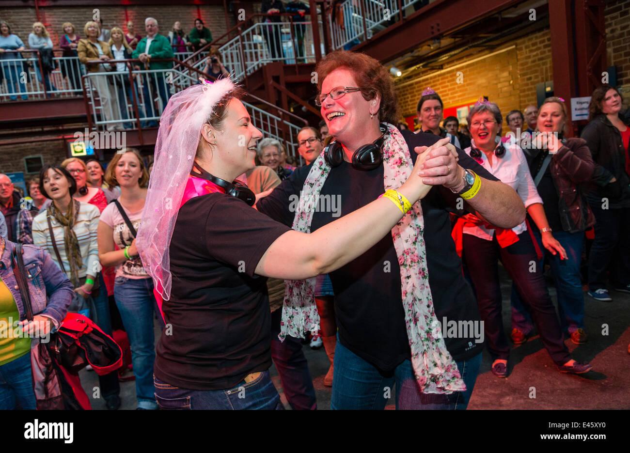 """Fröhliche Teilnehmer genießen """"Rudelsingen"""", kommen zusammen, um die jährliche Nacht der Stockbild"""